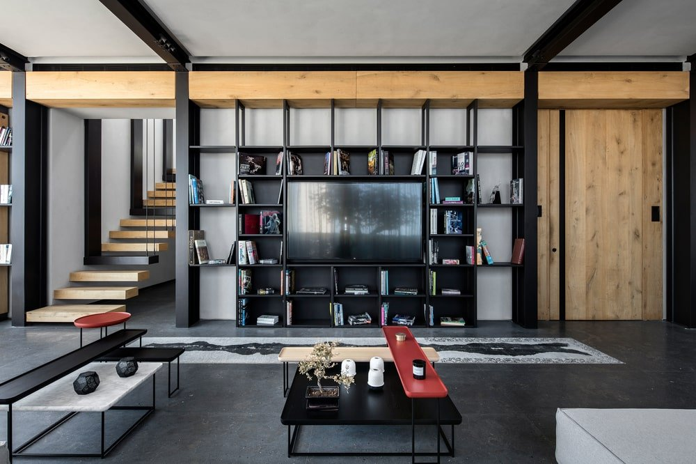 This is a close look at the black entertainment unit of the living room that has square shelves and supports the TV in the middle.