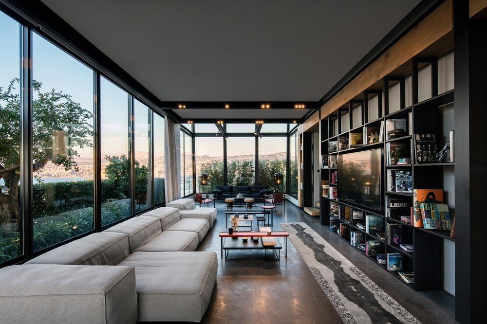 The living room is lit by the natural lights coming in from the two glass walls that bring in an abundance of natural lighting.