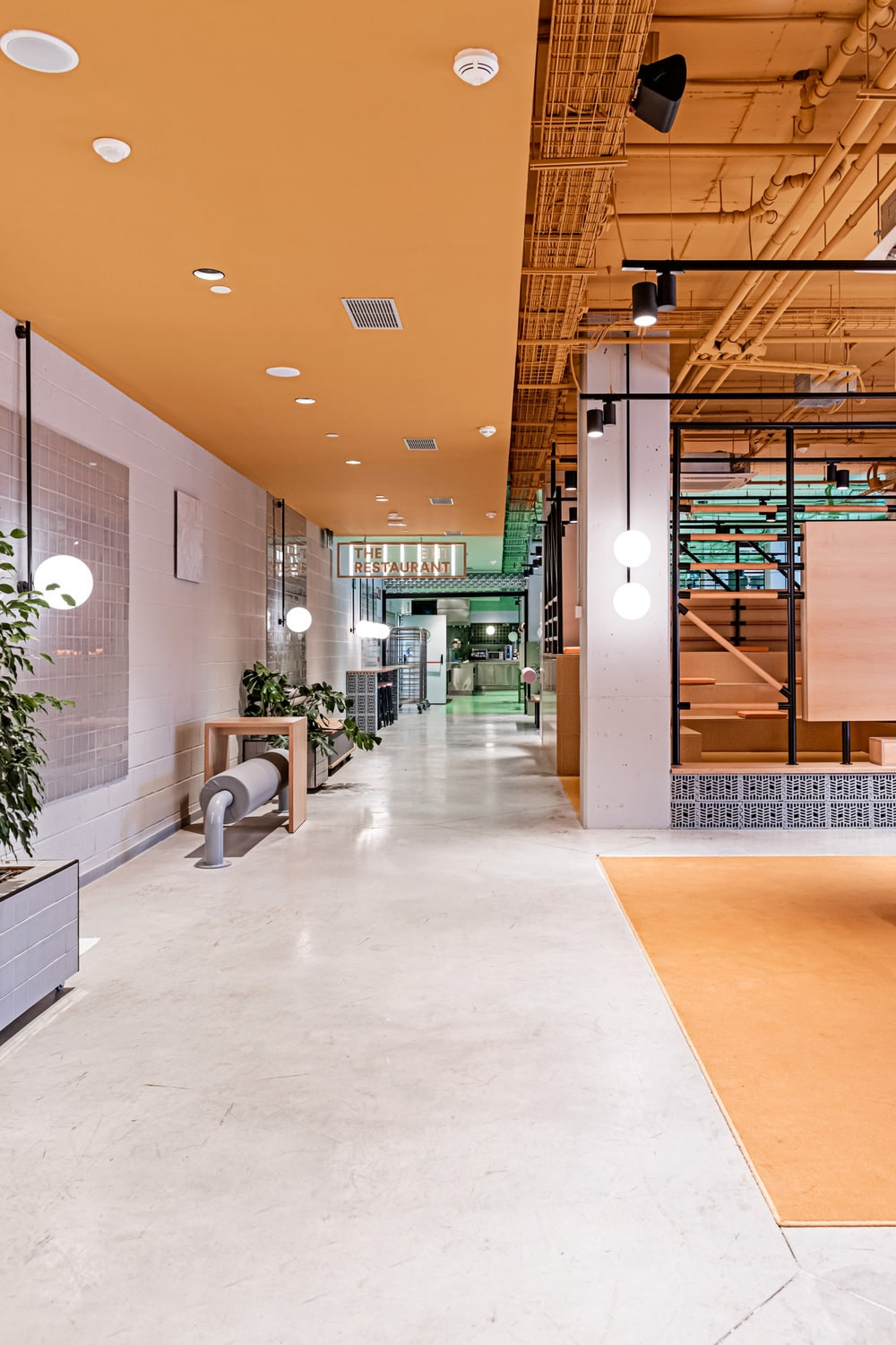 This is a large hallway inside the student residency with a colorful industrial-style design and bright subway tiles on the side leading to the restaurant.