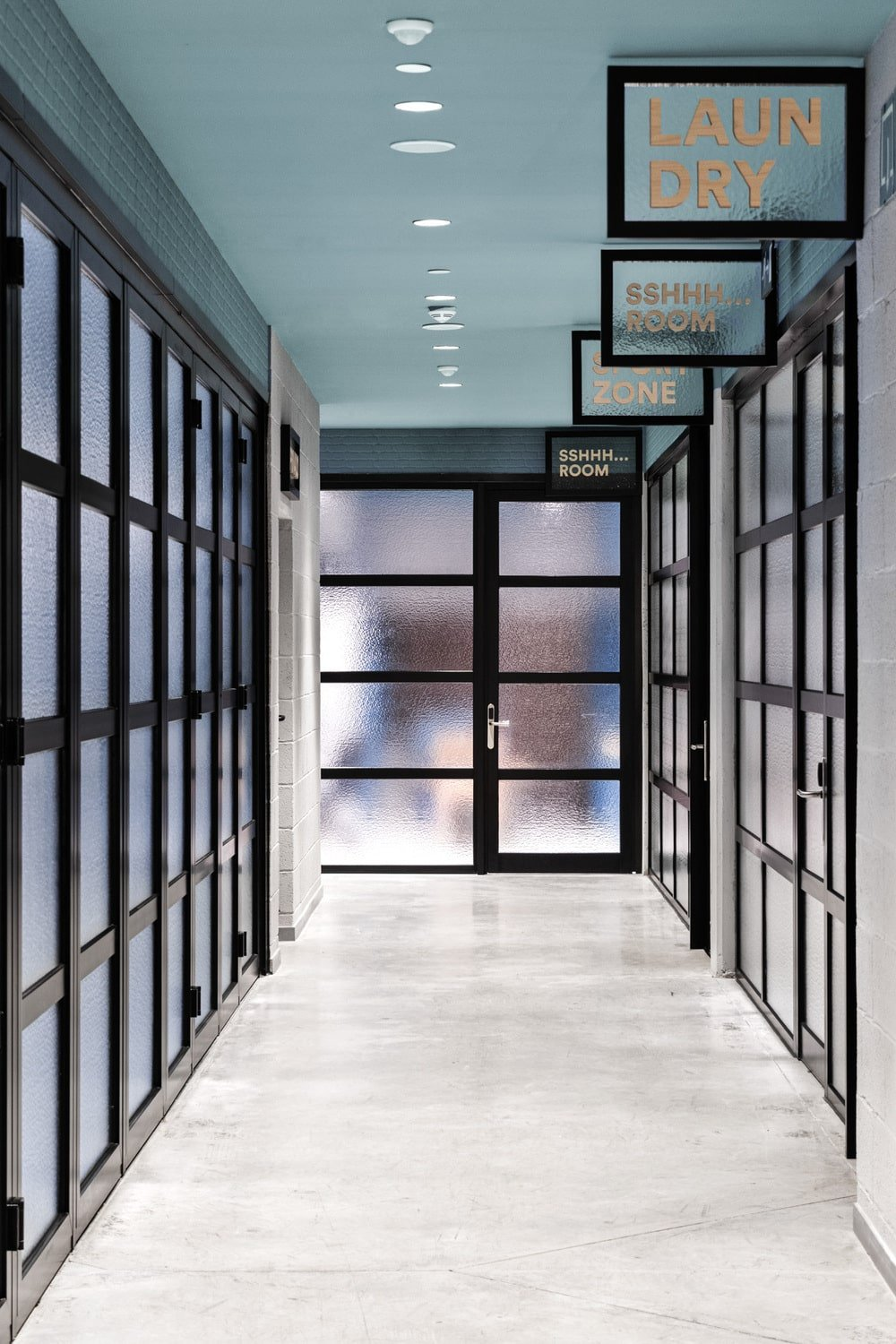 This is a hallway inside the student residency that has rows of forsted glass doors and walls on both sides to provide privacy.