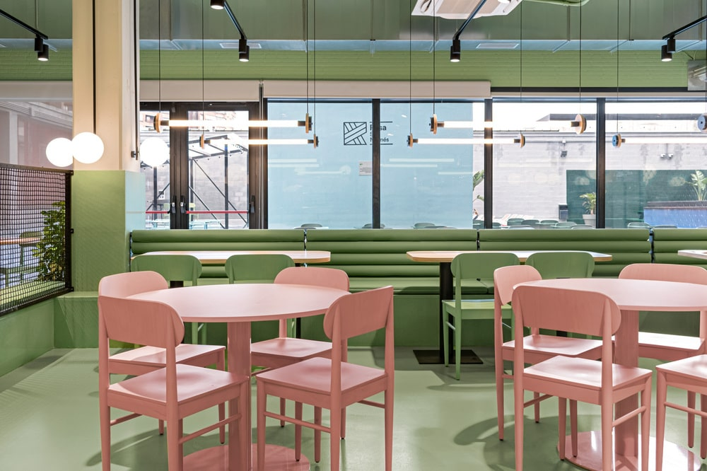 This is the a look at the dining area of the residency that has pink tables and chairs and green tone to its built-in structures.