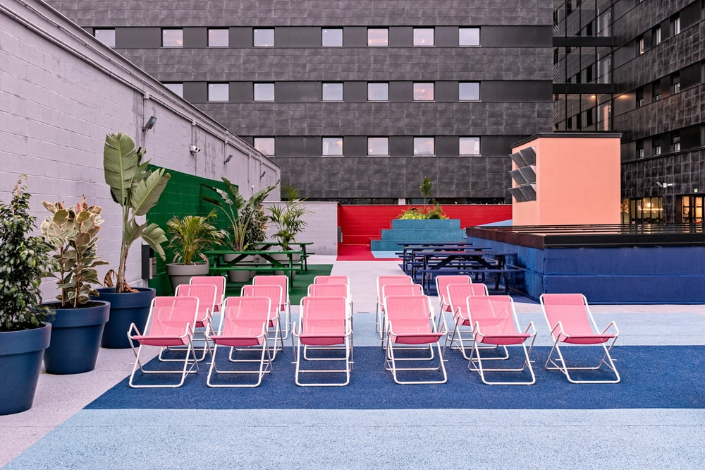 This is an outdoor area with multiple lounge chairs and potted plants.