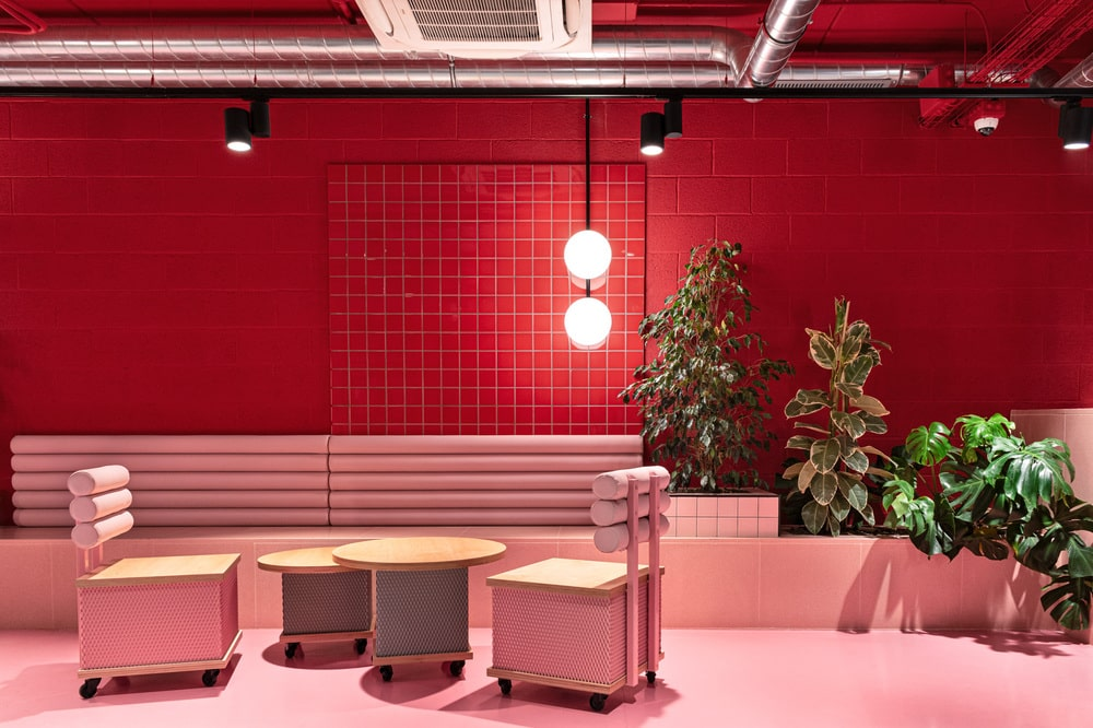 This is a close look at a section of the student residency that has built-in cushioned benches and coffee tables. These are then complemented by the red and pink tones.