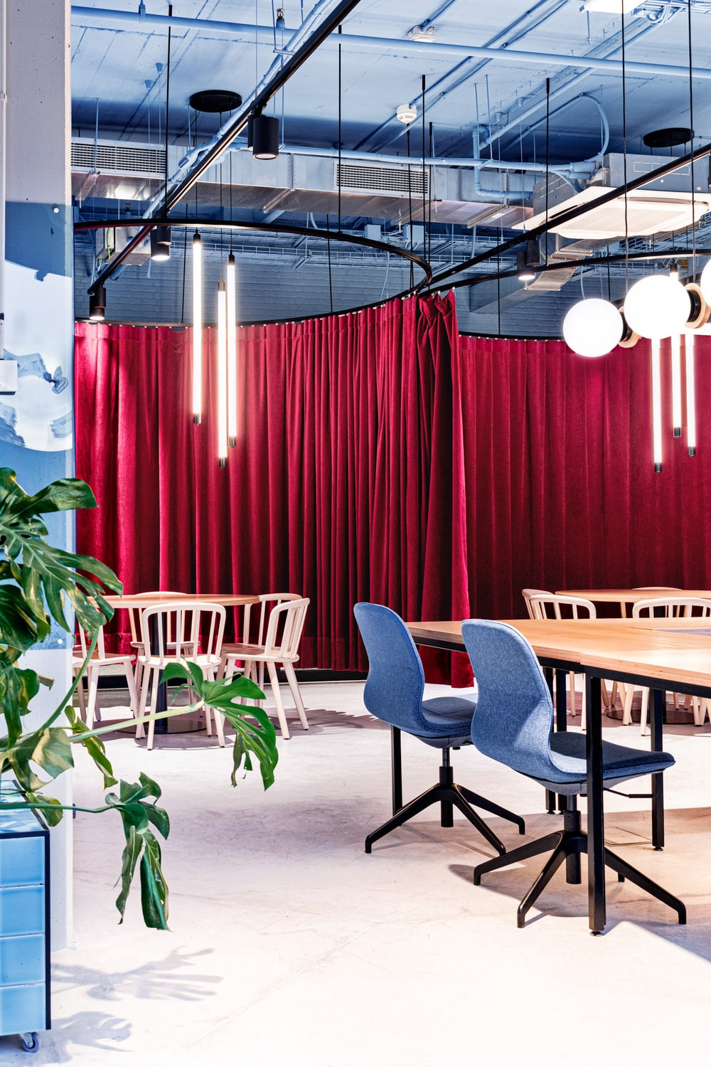 There are two curtained sections that has large round wooden tables paired with chairs and topped with lighting.