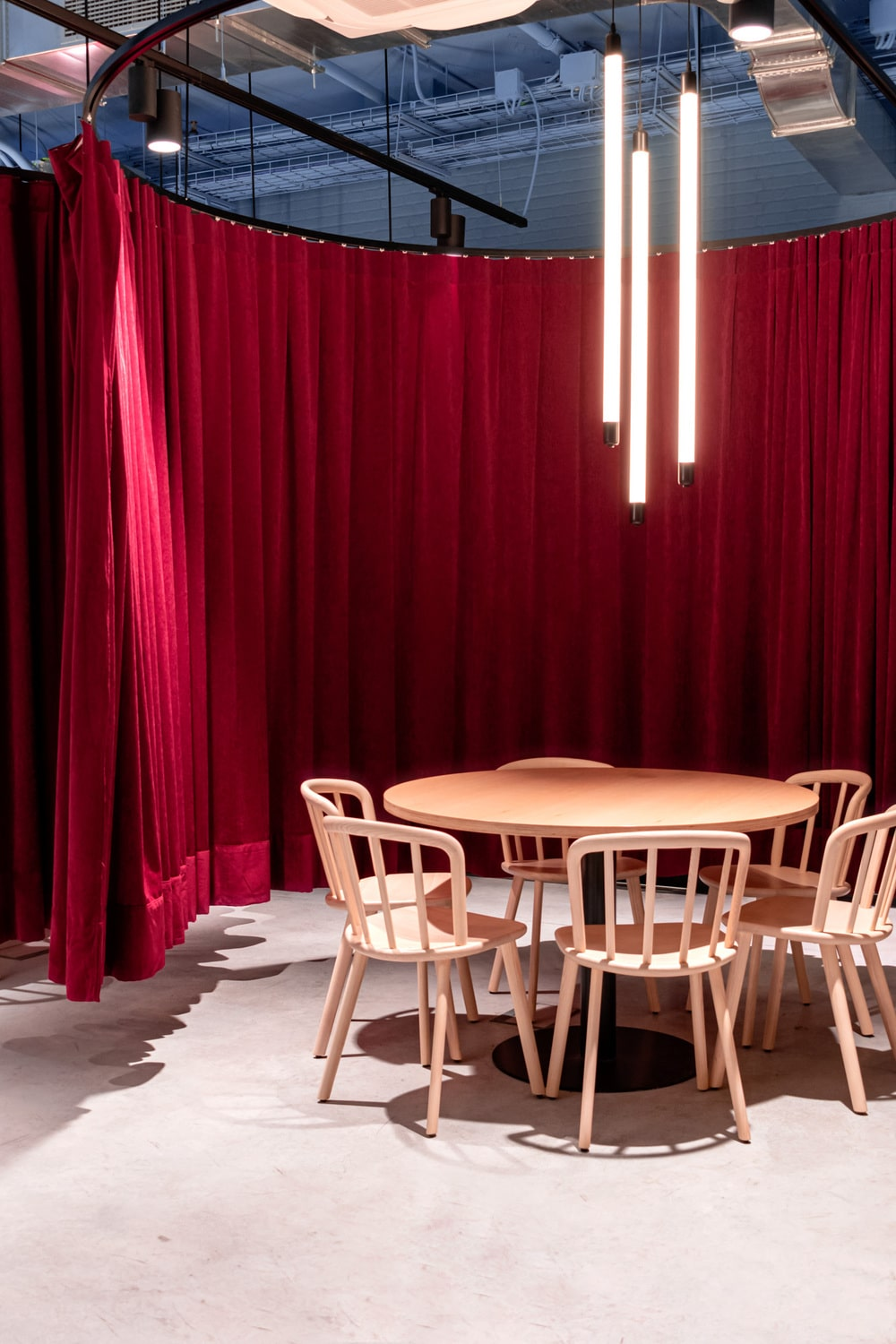 These meeting areas are bordered with red curtains that can dampen the sound and provide visual privacy.