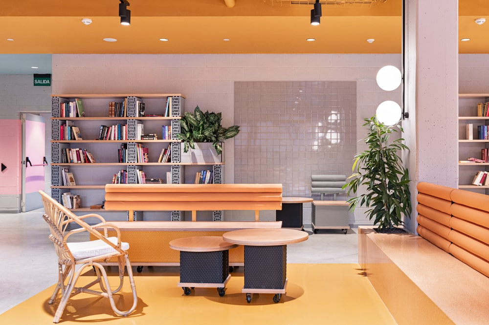 This is a look at the section of the sitting area with a built-in cushioned bench, a wooden chair and a couple of coffee tables complemented by the yellow tones and potted plants.