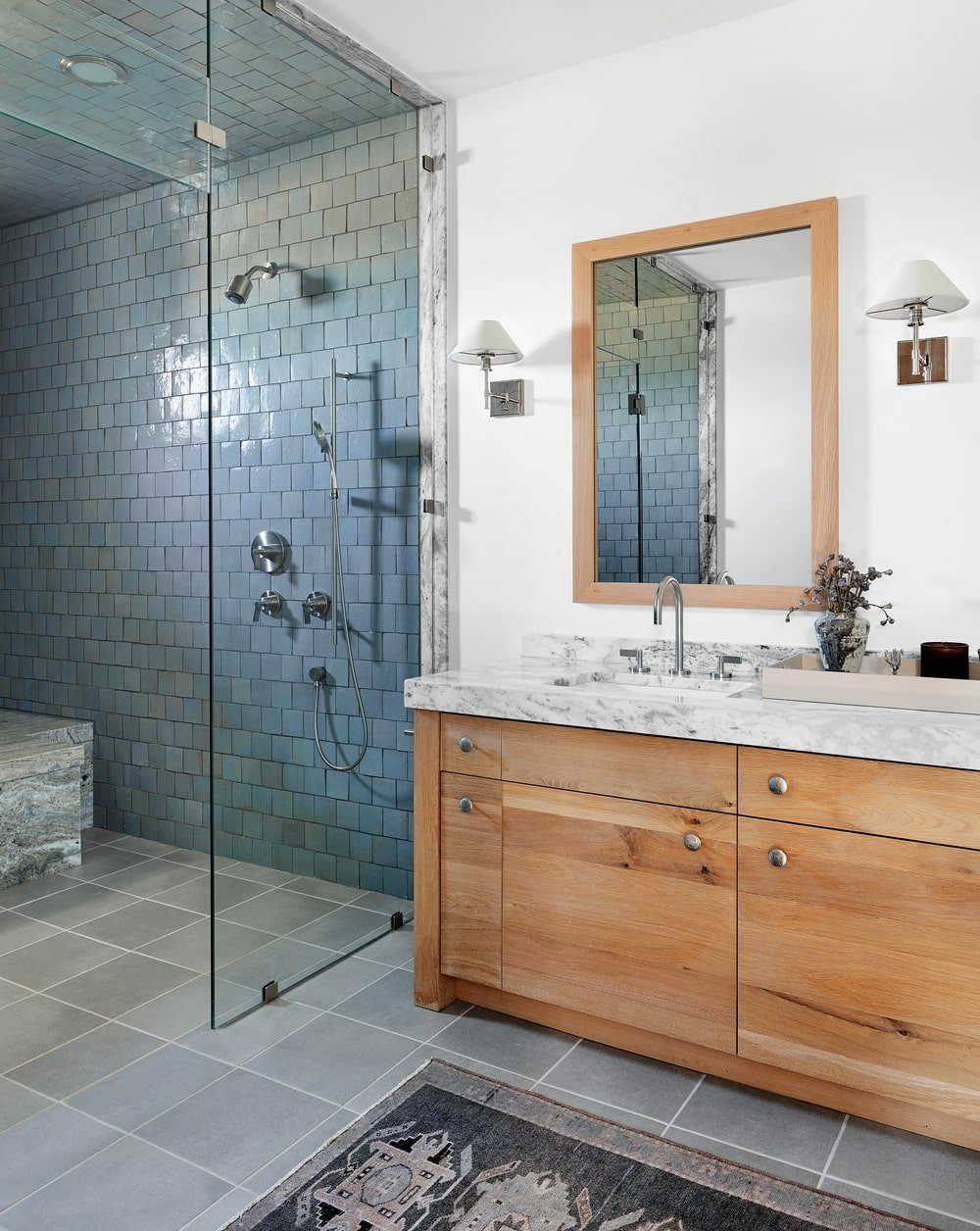This si a simple bathroom with a wooden vanity topped with a matching mirror beside the glass-enclosed shower area with dark tiles.