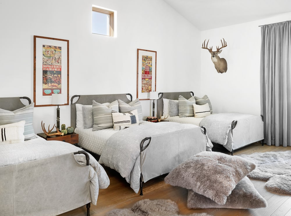 This is a kids' bedroom with multiple beds and a tall cathedral ceiling with transom window.