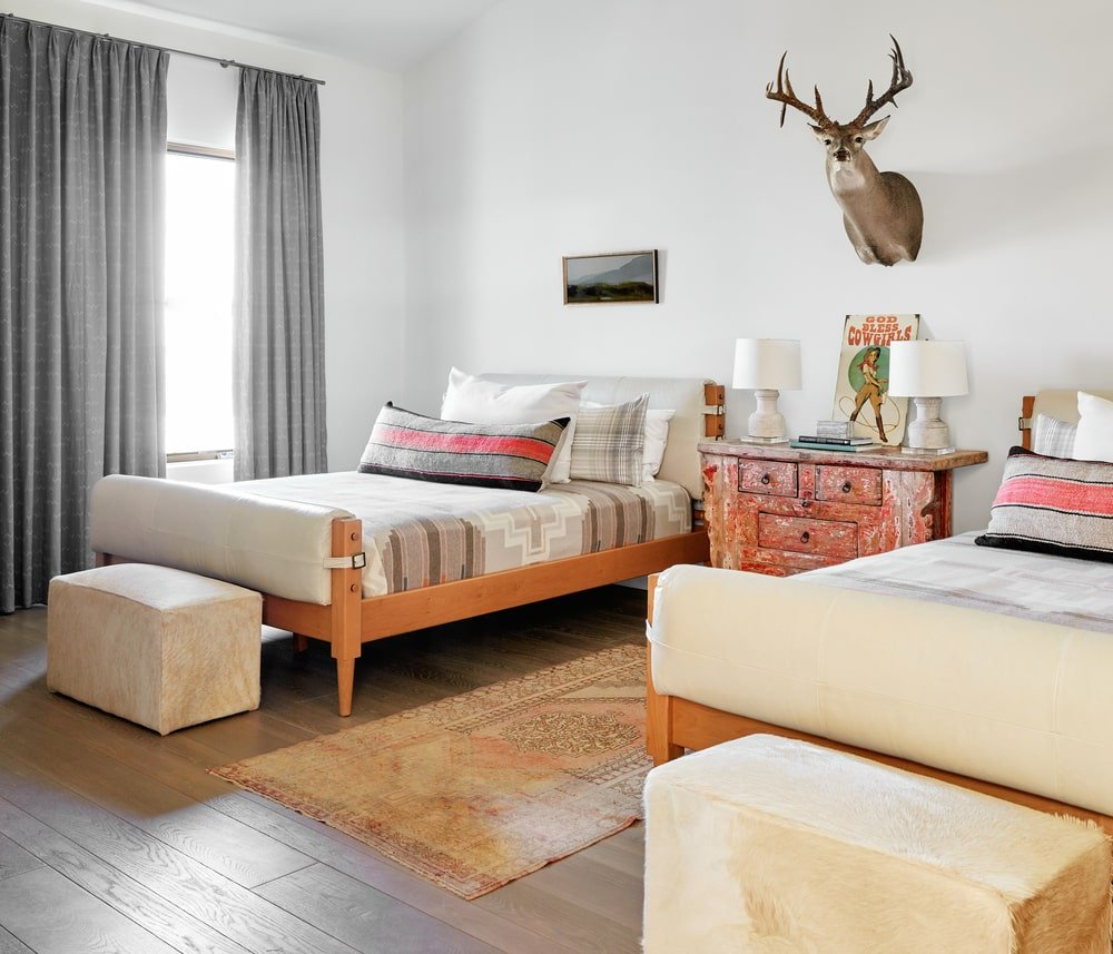 This bedroom has space for two beds with simple wooden frames that match the wooden dresser in the middle topped with a wall-mounted hunting trophy.