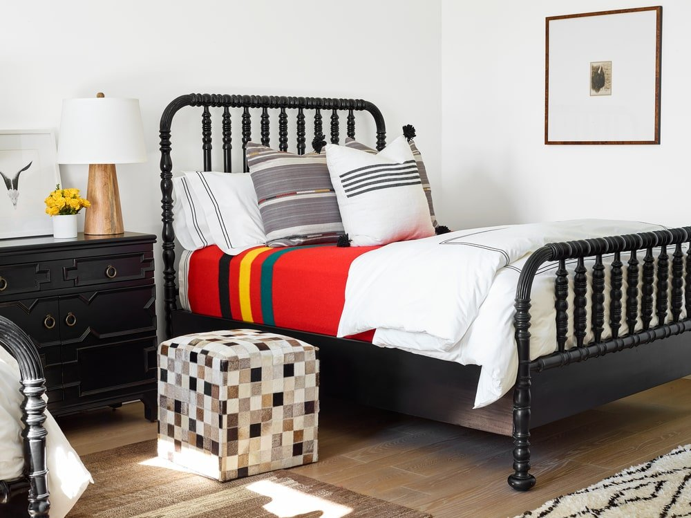 This bedroom is dominated by the dark wooden bed and dark wooden bedside drawer that contrast the white walls.