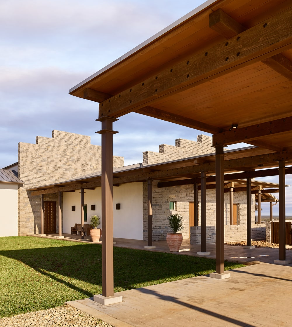 This is a look at the main entrance of the house with a rustic feel to its wooden cover over the walkway.