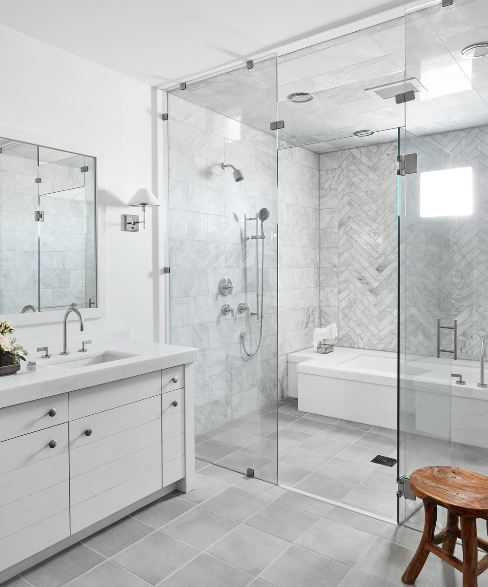 This is a bright bathroom with a white vanity and a glass-enclosed wet area of shower and bathtub on the far wall.
