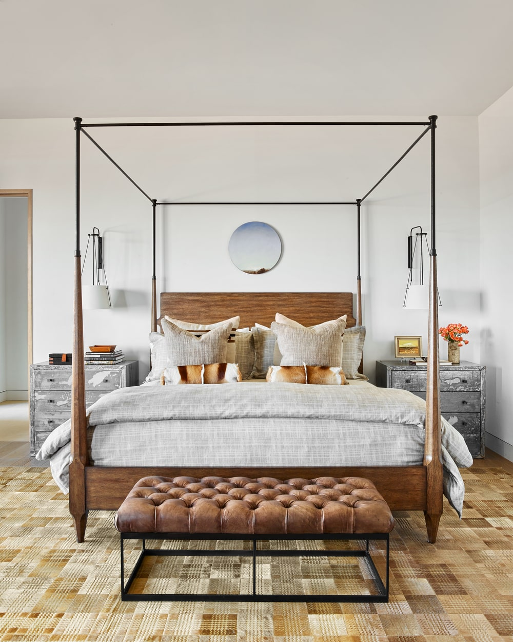 This is a look at the primary bedroom dominated by a large four-poster bed with a tufted bench at the foot and gray bedside drawers.