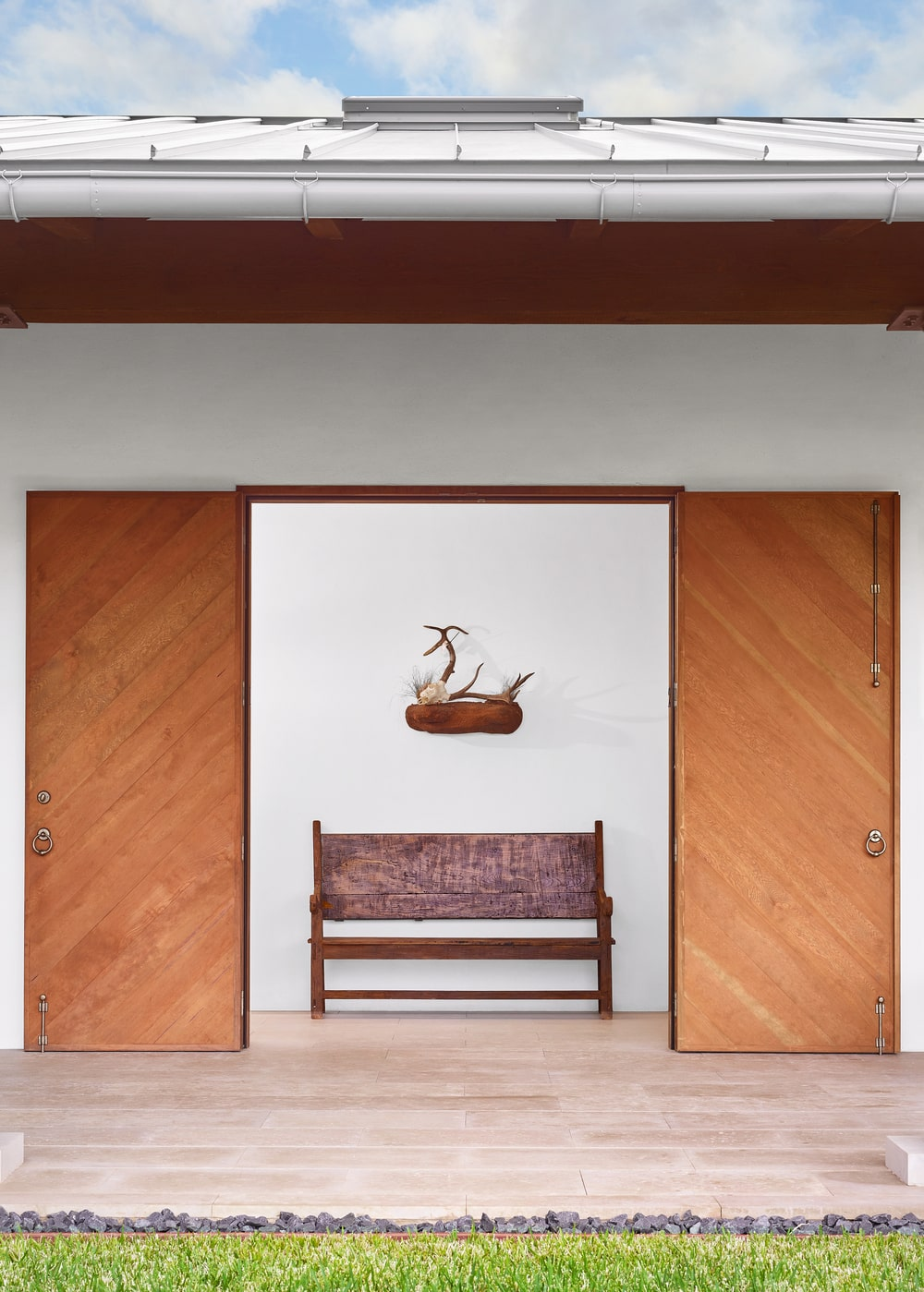This is a look at a hallway with a comfortable wooden bench adorned with a wall artwork above and flanked by wooden doors.