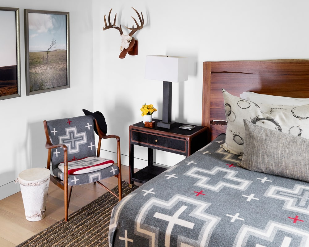 This is a close look at the bedroom that has patterned sheets to match the upholstery of the chair adorned with a dark bedside drawer and wall-mounted artwork.