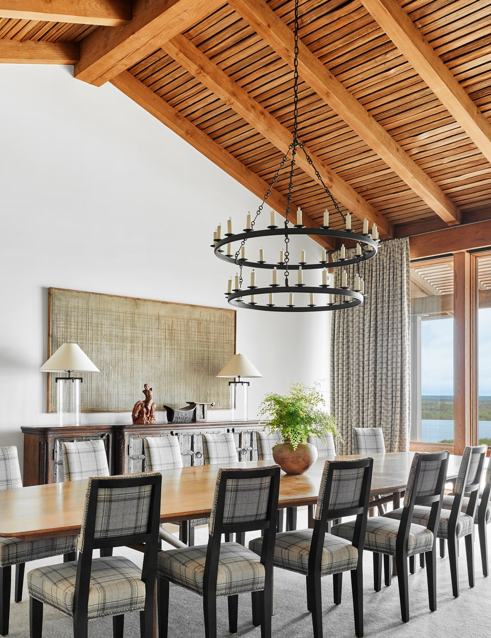 This is the dining area that has a large rectangular dining table topped with a large round two-tiered chandelier hanging from a tall cathedral ceiling with exposed wooden beams.