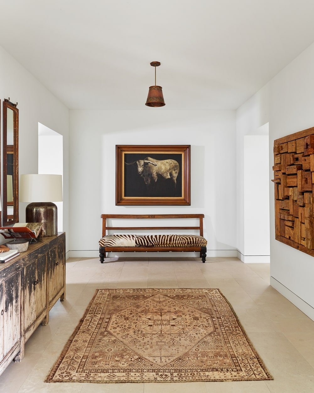 Upon entry of the house, you are welcomed by this foyer that has a console table on the side and wall-mounted artworks that stand out against the bright white walls.