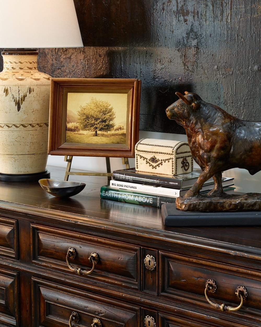 This is a close look at the brown wooden dresser adorned with various decors on top along with a table lamp.
