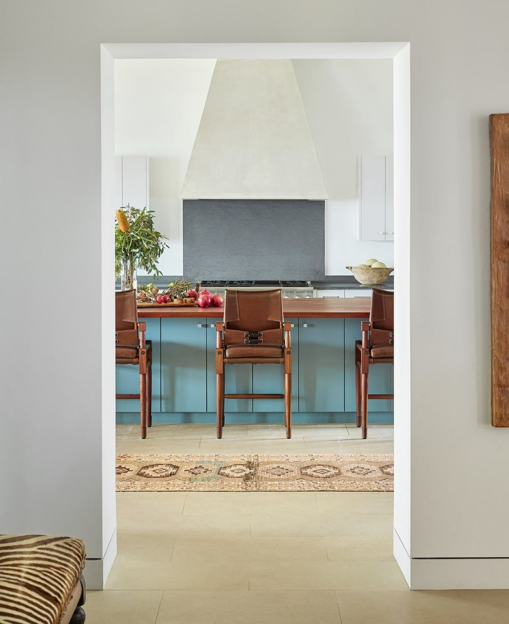 Through this entryway is the kitchen that has a breakfast bar paired with wooden stools.