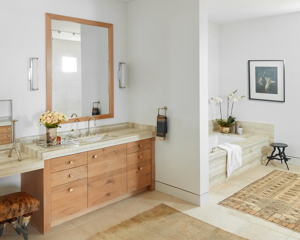 The bright and spacious bathroom has a wooden vanity topped with a mirror and a bathtub on the other side of a half wall topped iwth a wall-mounted artwork and a flower vase.