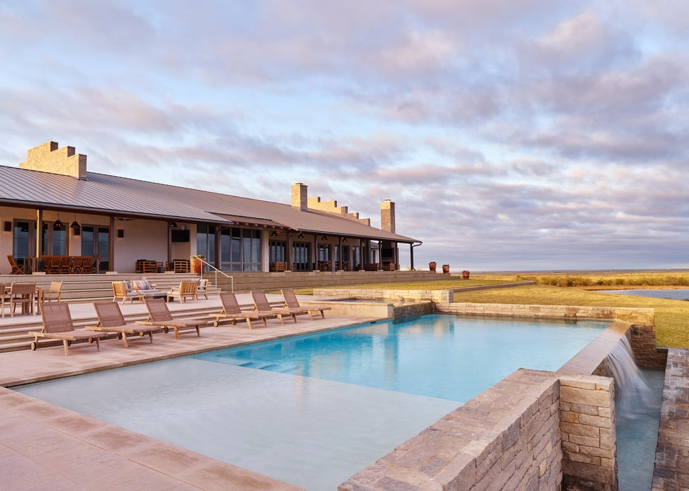 This is a view of the back of the house with a large pool and lounge chairs by the poolside area.