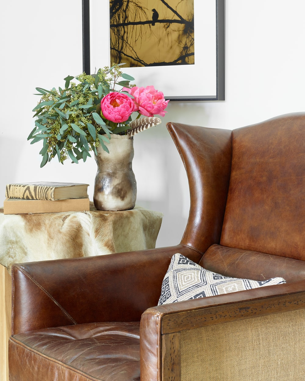 This is a close look at a comfortable reading nook with a leather armchair beside a small side table.