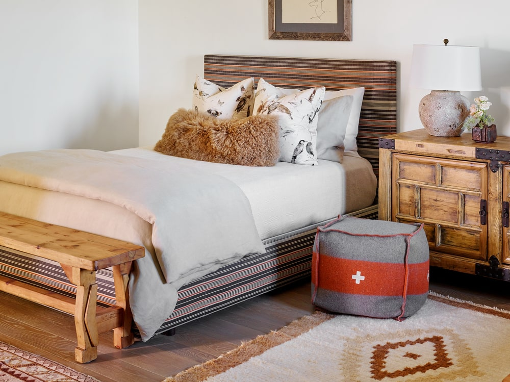This bedroom has a rustic-style bed to match the wooden bedside drawer and wall-mounted mirror above.