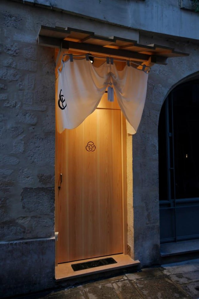 This is a nighttime view of the main door of the store that has a warm lighting to give the main entrance a certain inviting look.