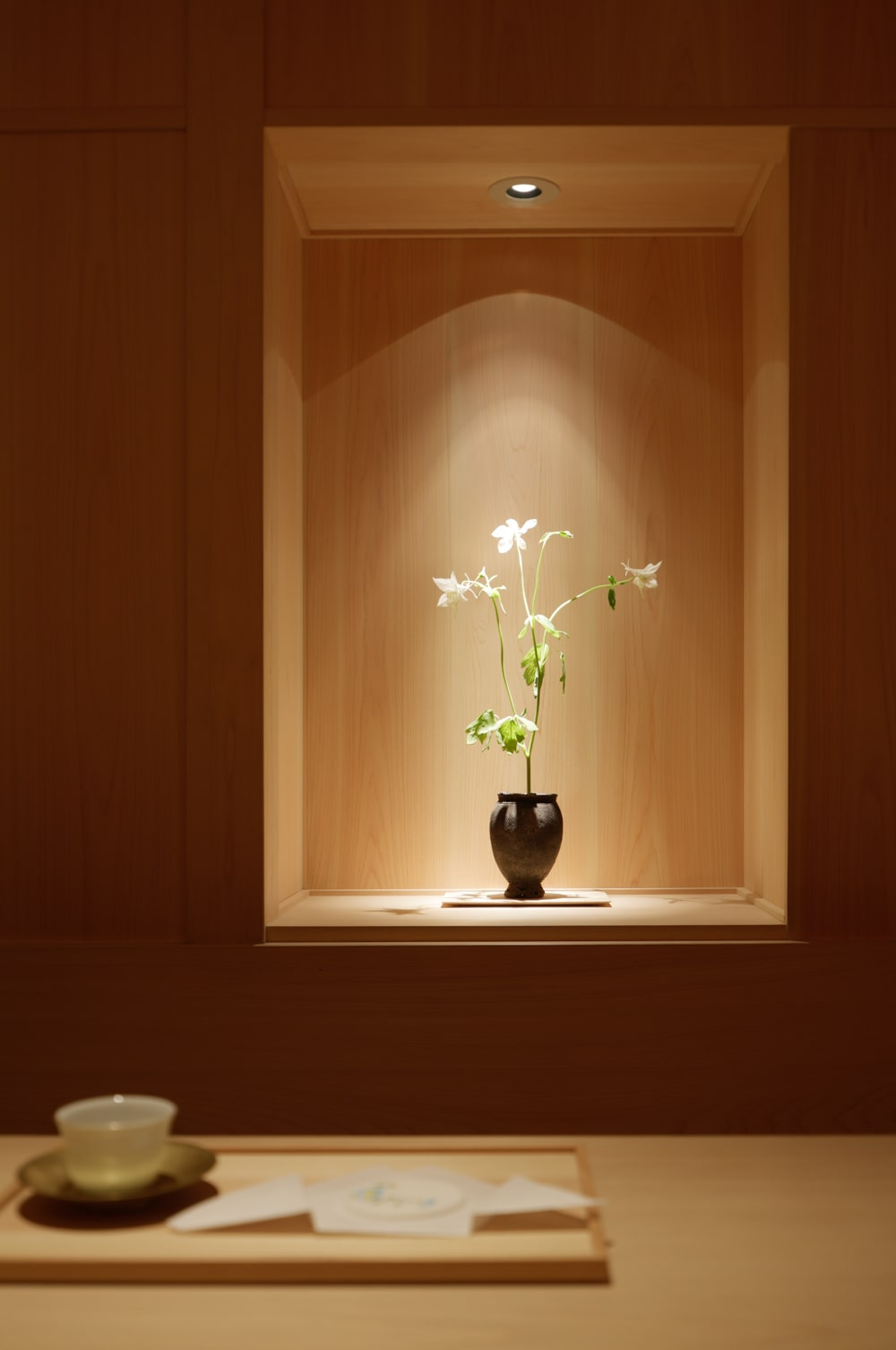 This is an alcove decoration fitted with a flower vase above the bench of the waiting customers.