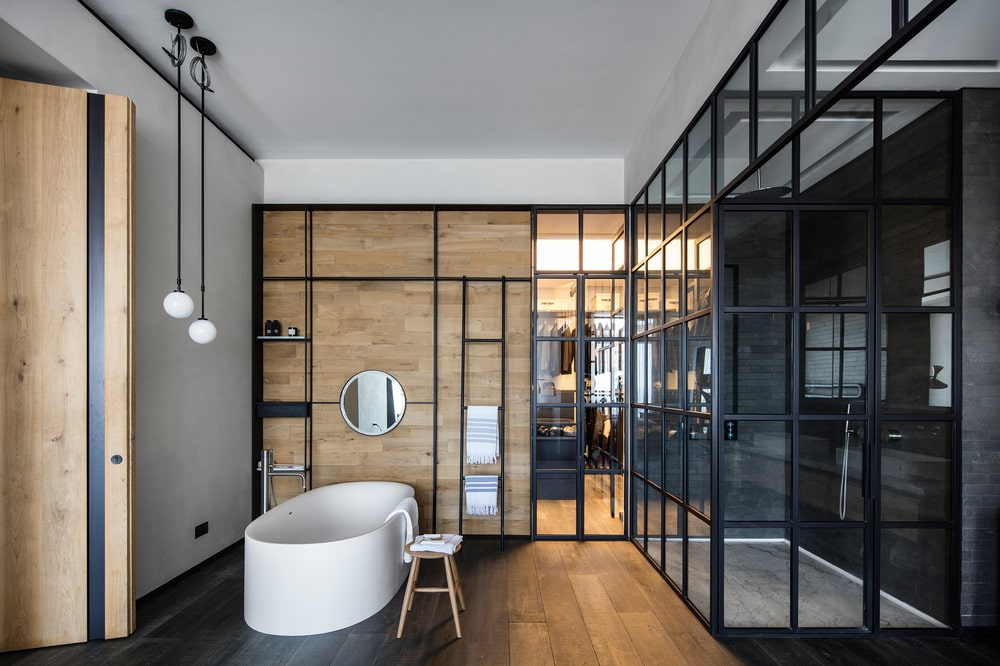 This is a close look at the bathroom that has a glass-enclosed shower area with black frames to match the dark flooring and a freestanding bathtub that stands out.