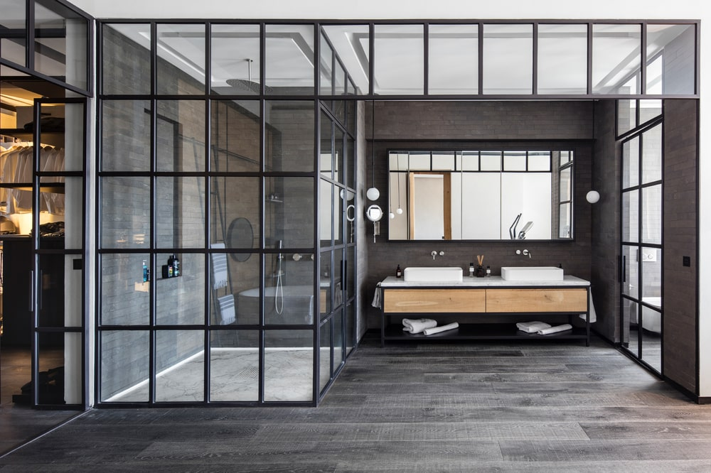 On the side of the glass-enclosed shower area is the two-sink floating vanity topped iwth a wide wall-mounted mirror on a dark wall.