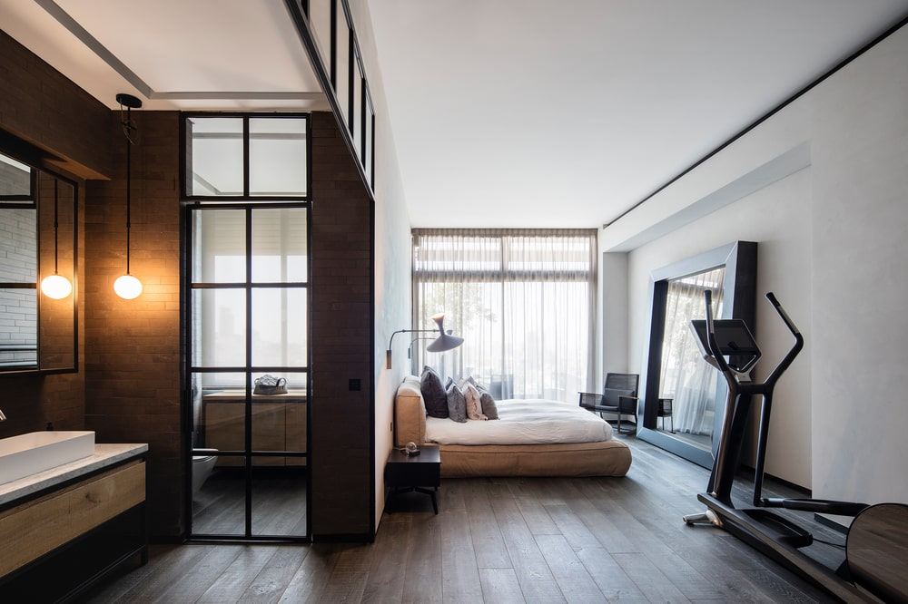 The primary bedroom has a platform bed on the far side by the large window that is sharing a wall with the shower room behind the wall of its headboard.