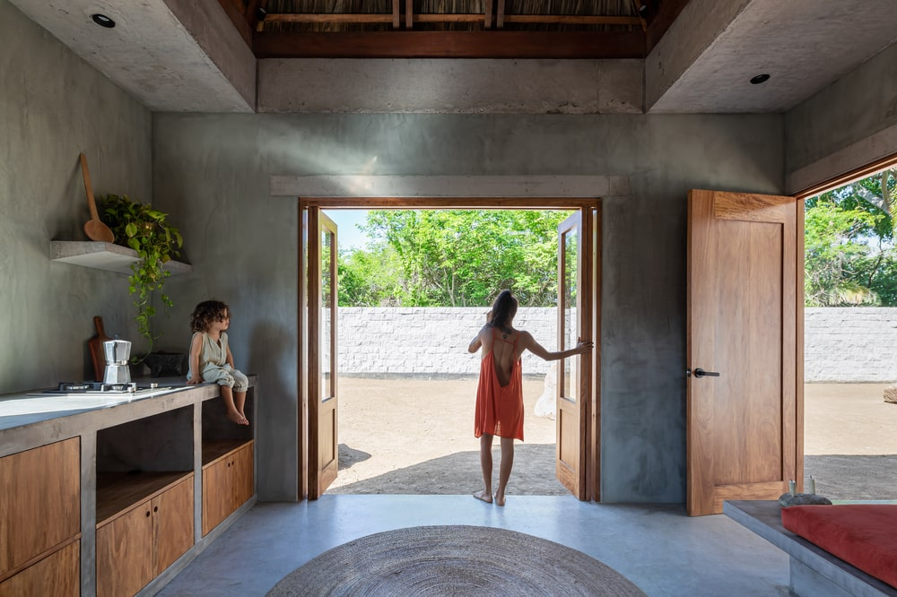 This is a look at the concrete counters and structure of the kitchen by the large open wall with foldable doors.