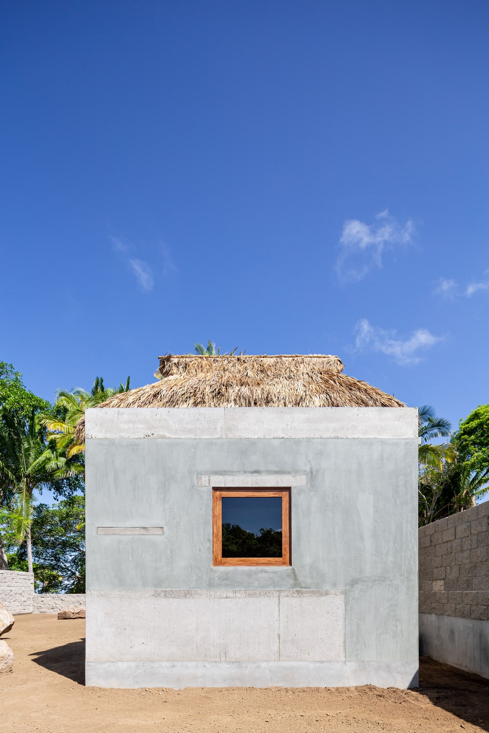 This is a look at the house's elevation that shows the concrete exterior walls and palm roof.