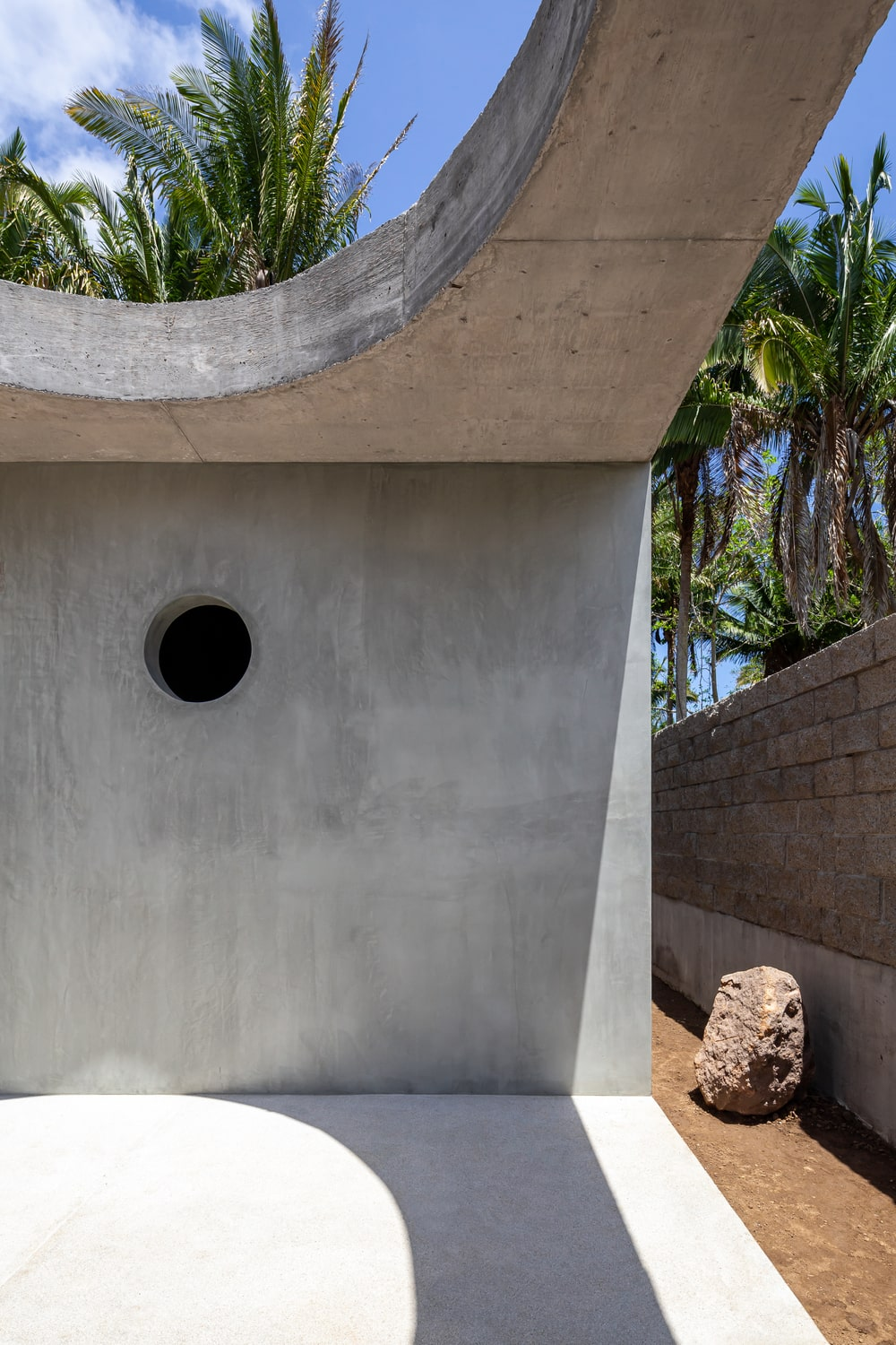 This is a close look at the concrete wall with a round hole that serves as a ventilation window.