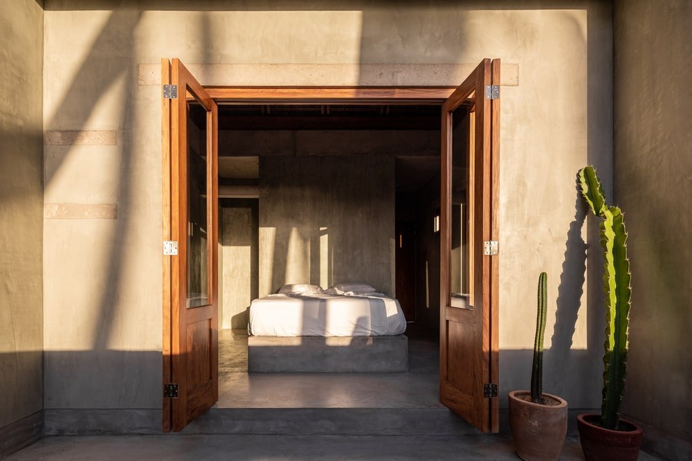 This is exterior view of the section of the house looking into the bedroom with concrete walls, wooden doors and cacti on the side.