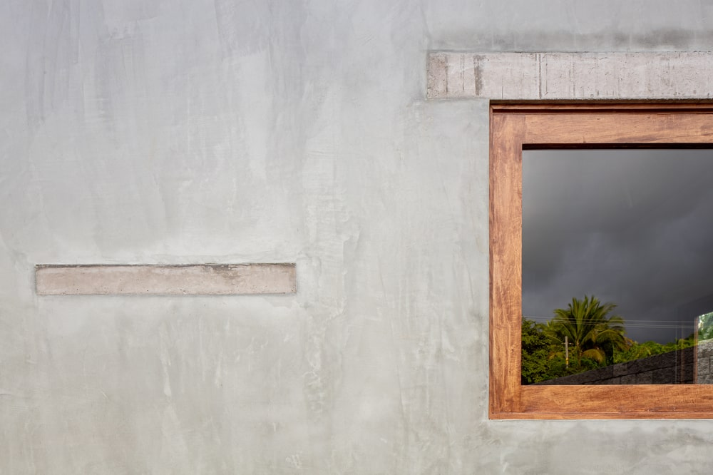 This is a close look at the concrete exterior wall and the wooden frame of the window that stands out.