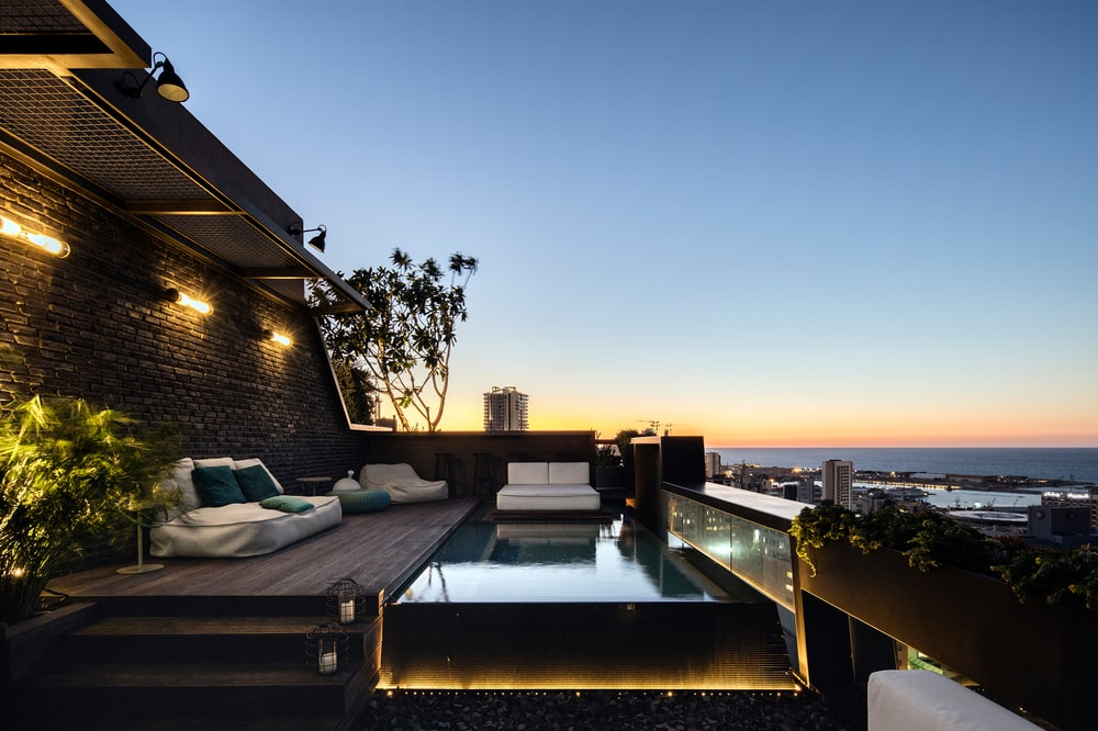 This is a balcony pool with wooden walkways and lounge sets on the side to enjoy the view.