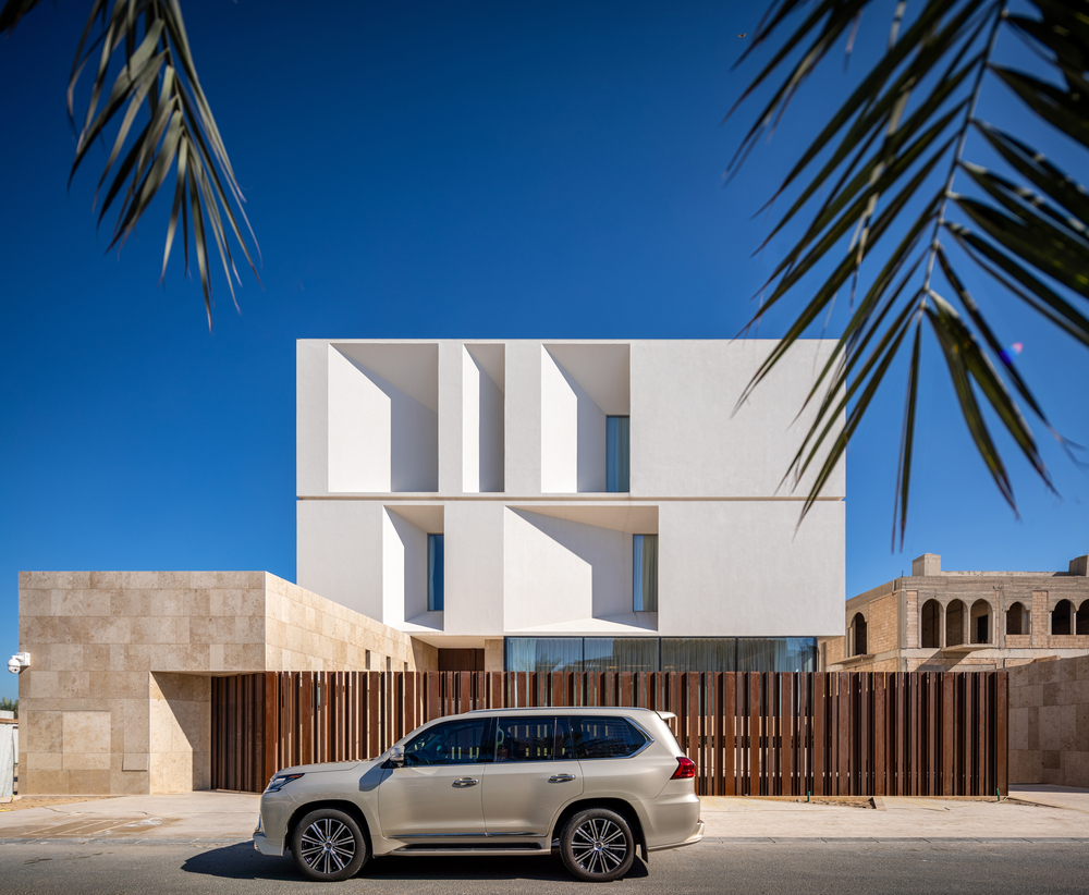 This is a look at the front of the house that has brown slat fences and bright white modern exterior walls.