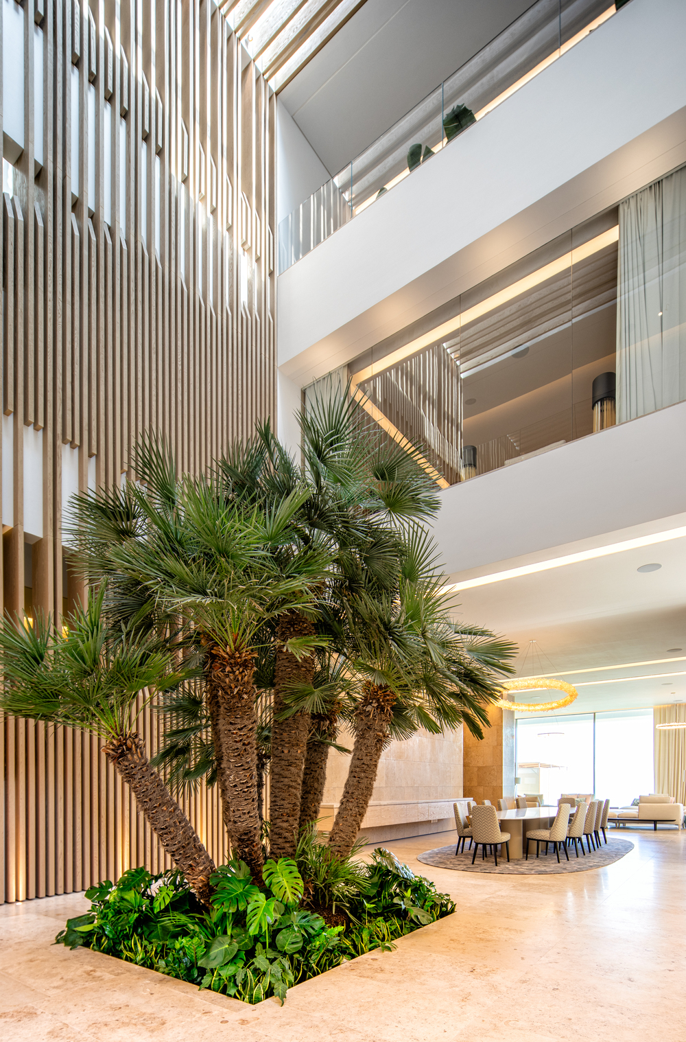 This is a view of the dining area adorned with a large cluster of tropical trees in an indoor garden.