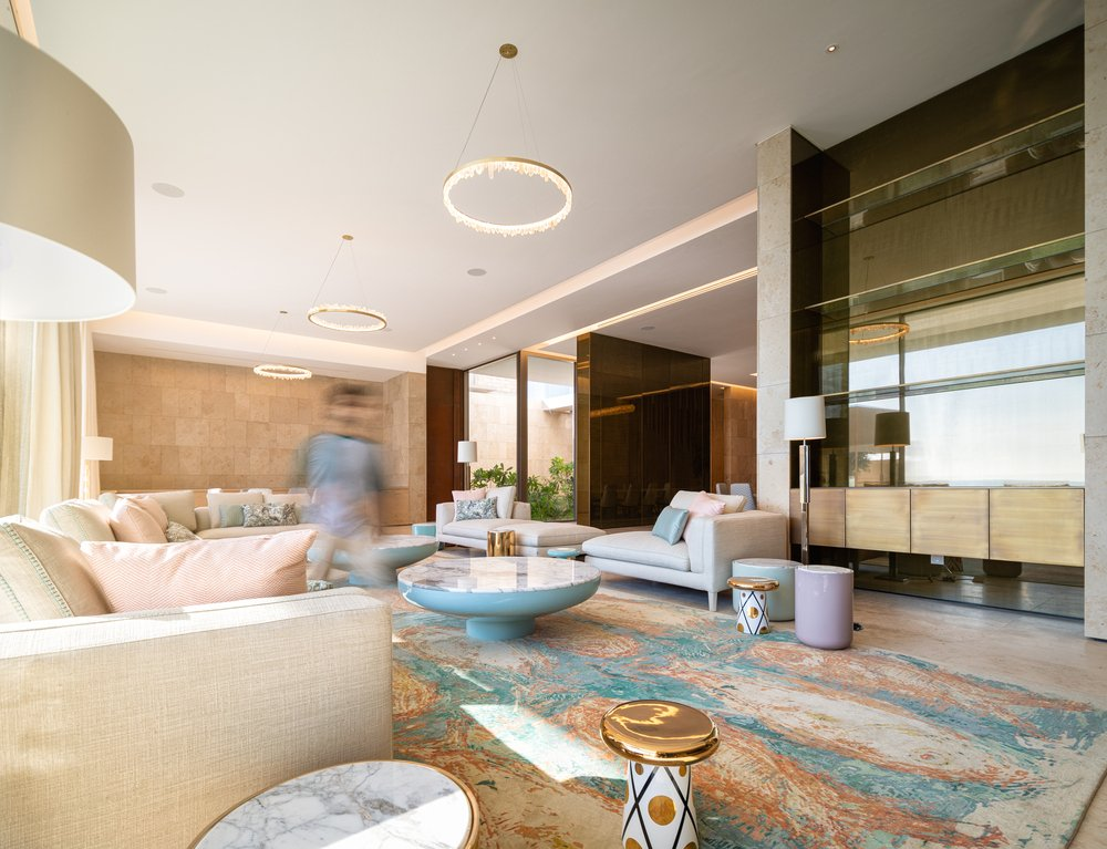 The large living room has beige sofas and colorful area rugs that pair well with the pastel tones of the coffee tables.