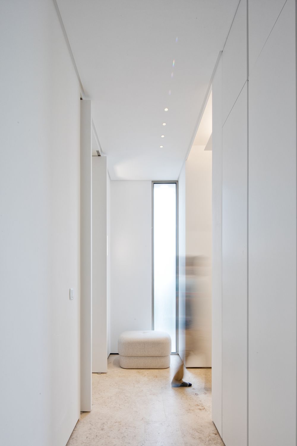 This is a simple and bright white hallway with white walls and ceiling brightened by the window on the far wall with a small ottoman.
