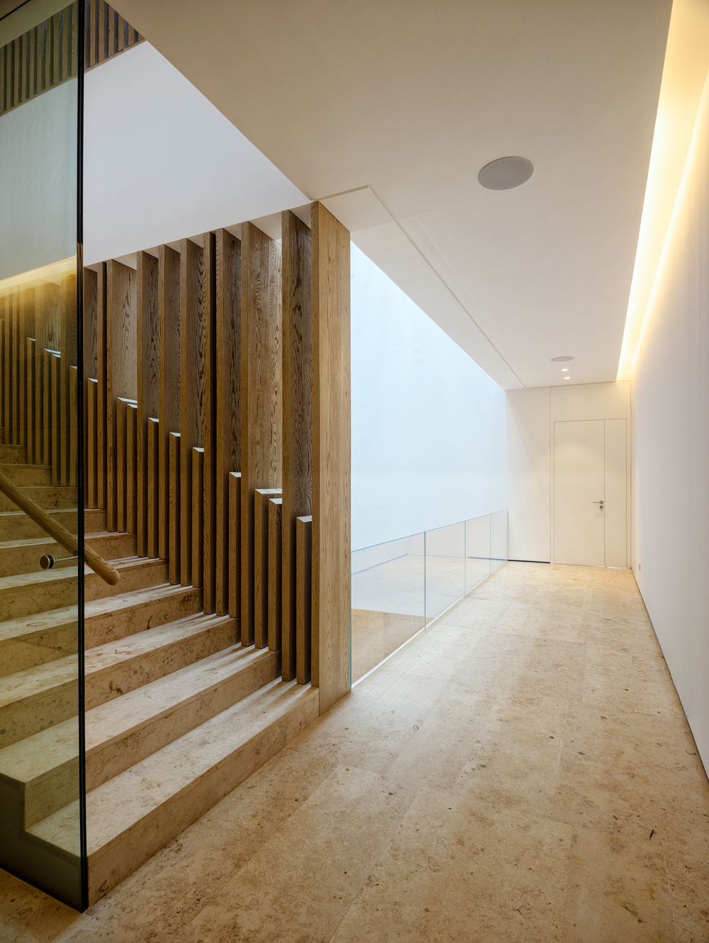 This is a view of the indoor balcony by the staircase landing that has brown marble floors.