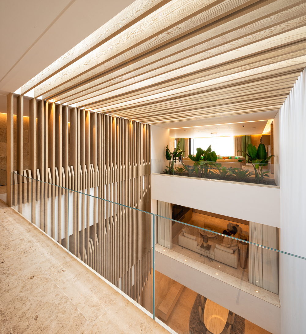 This is a view of the indoor balcony that has glass railings and patterned slat walls and ceiling.