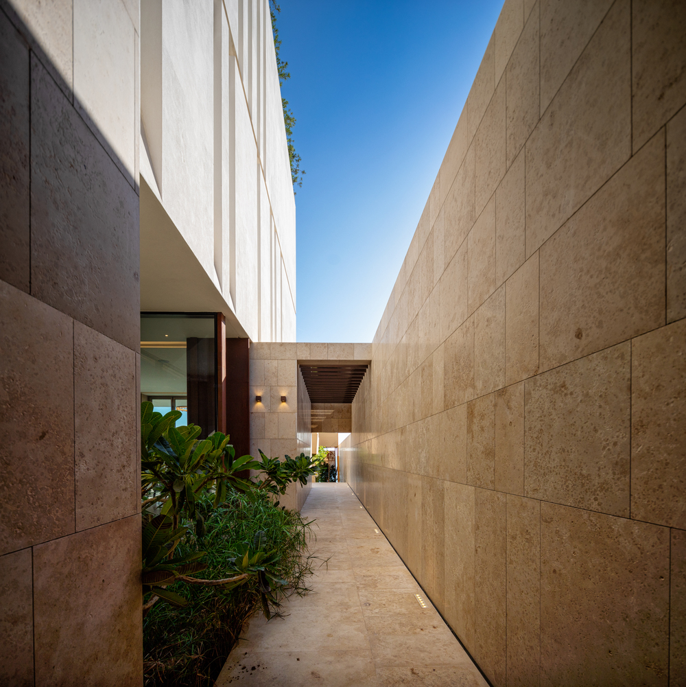 This is an outdoor narrow walkway of the house with brown marble walls.