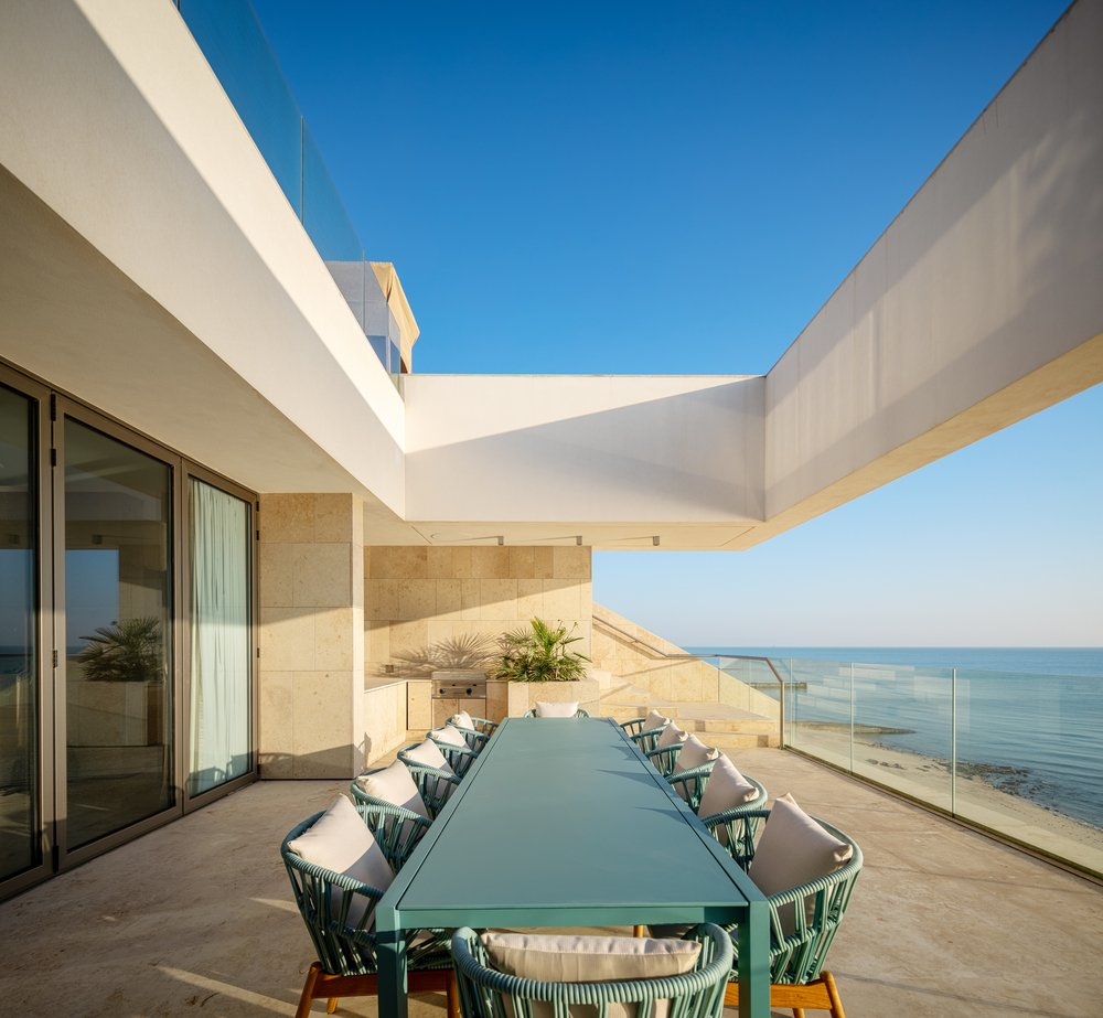 This is the outdoor dining area with a large rectangular dining table topped with a large beige concrete structure.
