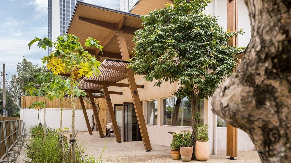 The main entrance is adorned with various potted plants and medium-sized trees.
