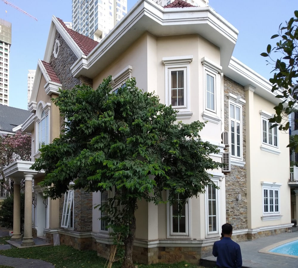 This is a look at the house with beige exterior walls, pillars and tall windows.