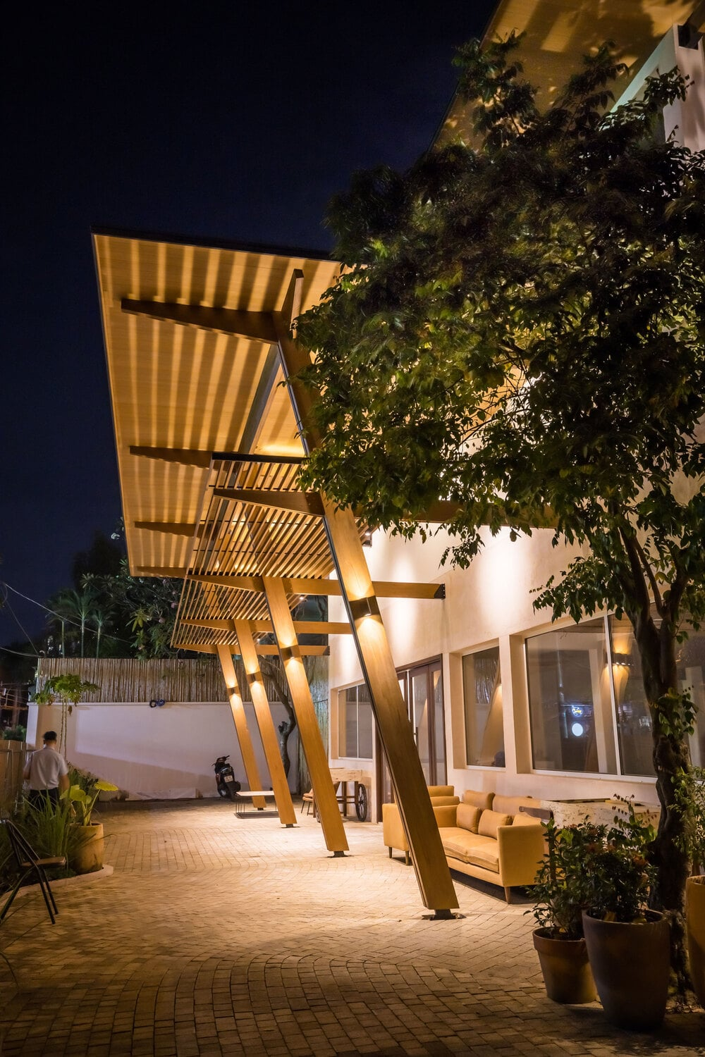 This is a nighttime view of the house exterior with warm lighting and comfortable outdoor sofa facing the landscape.