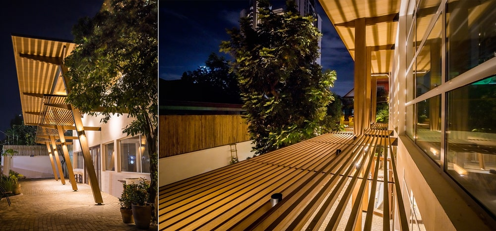 This is a dual view of the unique architectural wooden structure that is lit with warm outdoor lighting.